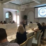 2018 Leadership Retreat, Palm Beach – female member standing at head table in front of large projection screen