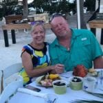 2019 In-state retreat, Key Largo – member and wife posing for photo at table on beach