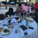 2019 In-state retreat, Key Largo – members and family posing for photo at table on beach