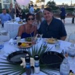 2019 In-state retreat, Key Largo – two members posing for photo at table on beach