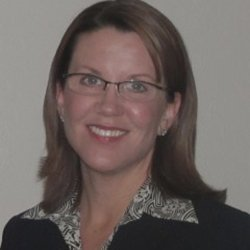 Kathryn Hill - Young caucasian woman with light brown hair and blue eyes wearing glasses and a black jacket and patterned collared shirt