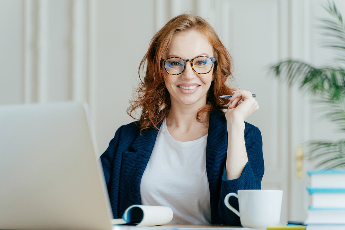 Glad redhead curly woman works freelance, uses laptop computer, writes down notes in notepad, drinks coffee, wears optical glasses, being in good mood, develops business company. Work concept